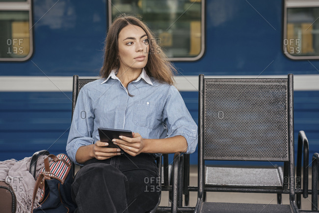 Young female traveler waiting on station- using e-book