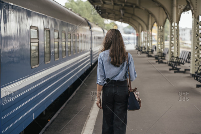 Rear view of young female traveler walking on the platform