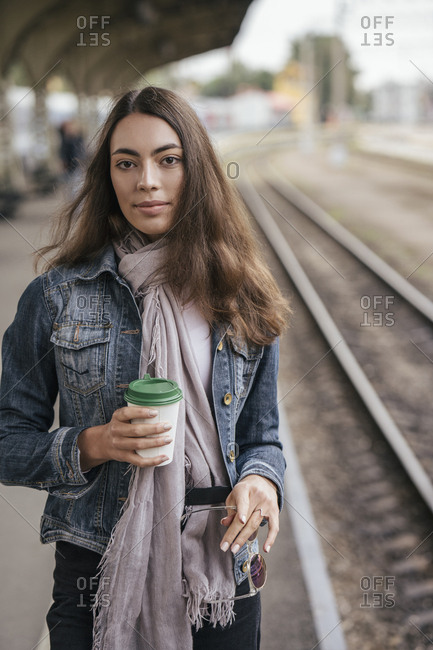 Young female traveler with coffee to go on train station