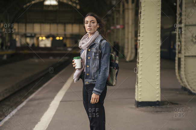 Young female traveler with coffee to go on the platform