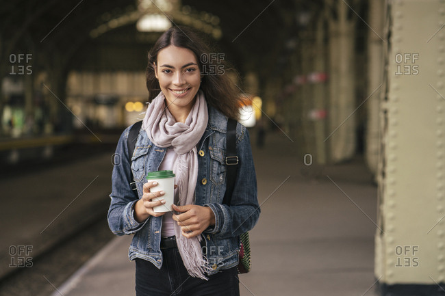 Young female traveler with coffee to go on the train station