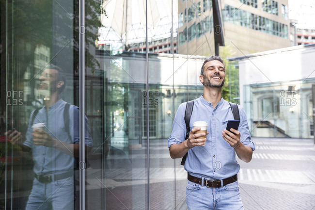 Smiling businessman holding cup of coffee and smartphone in the city- Berlin- Germany