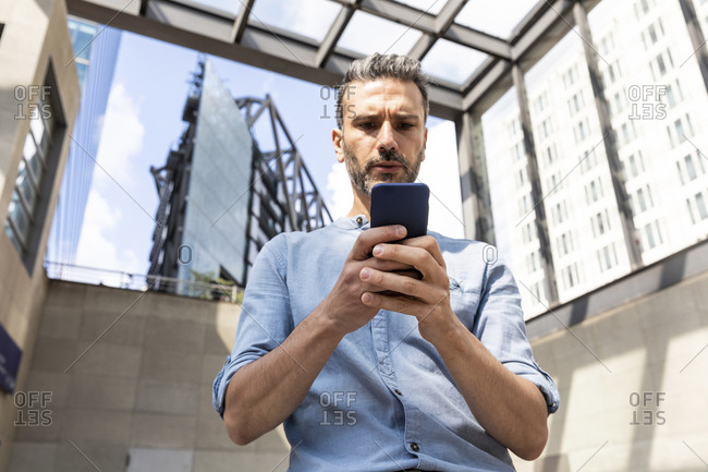 Serious businessman looking at the smartphone in the city- Berlin- Germany