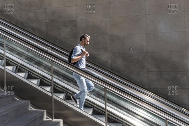 Businessman walking down escalator in the city