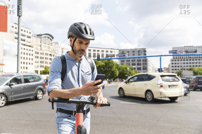 Businessman looking at the smartphone commuting on electric scooter in the city- Berlin- Germany