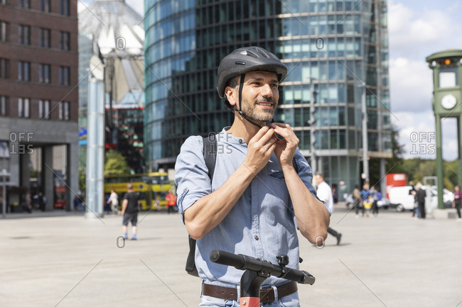 Man fastening the helmet before riding on electric scooter- Berlin- Germany