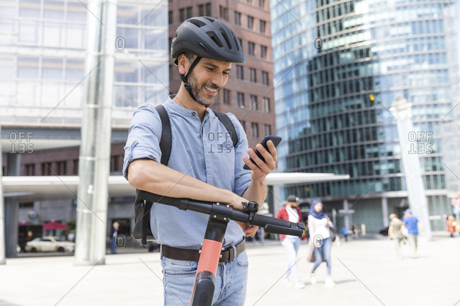 Smiling businessman looking at the smartphone commuting on electric scooter in the city- Berlin- Germany