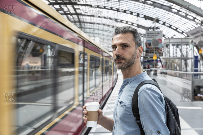 Man with takeaway coffee at the station while train coming in