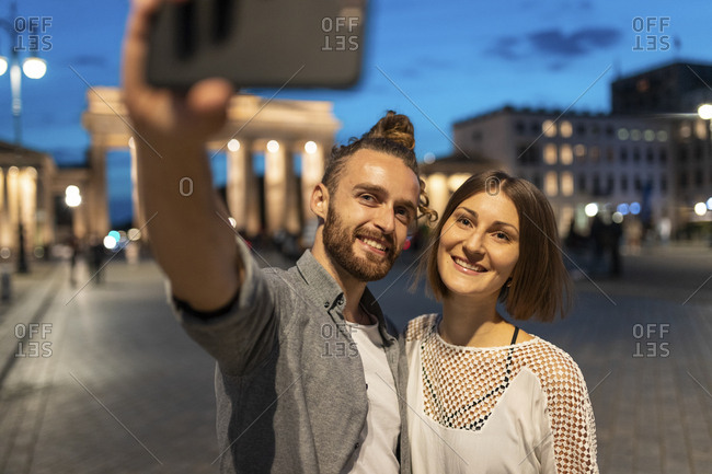 Happy couple taking a selfie at Brandenburg gate at blue hour- Berlin- Germany