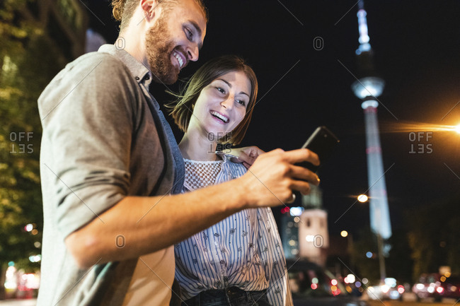 happy couple using smartphones in the city at night- Fernsehturm in the background- Berlin- Germany