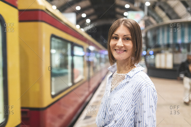 Young smiling woman on train station with blurred train in the background