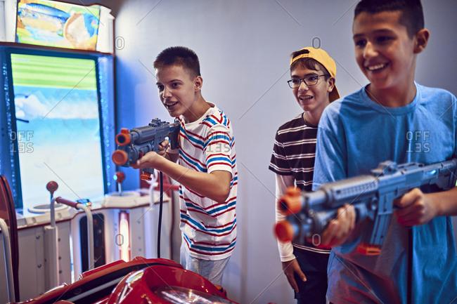 Teenage friends shooting with guns in an amusement arcade