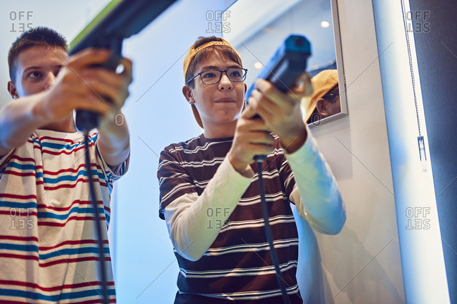 Teenage friends shooting with pistols in an amusement arcade
