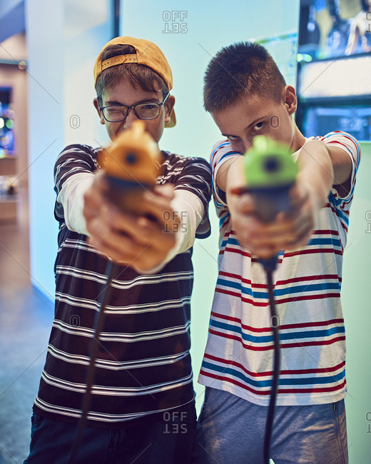 Portrait of teenage friends shooting with pistols in an amusement arcade