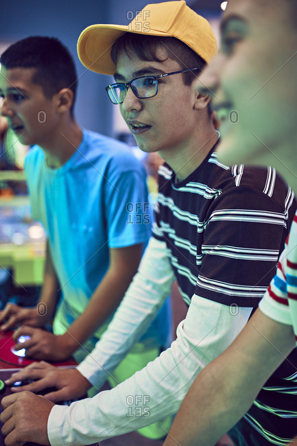 Teenage friends playing with a gaming machine in an amusement arcade