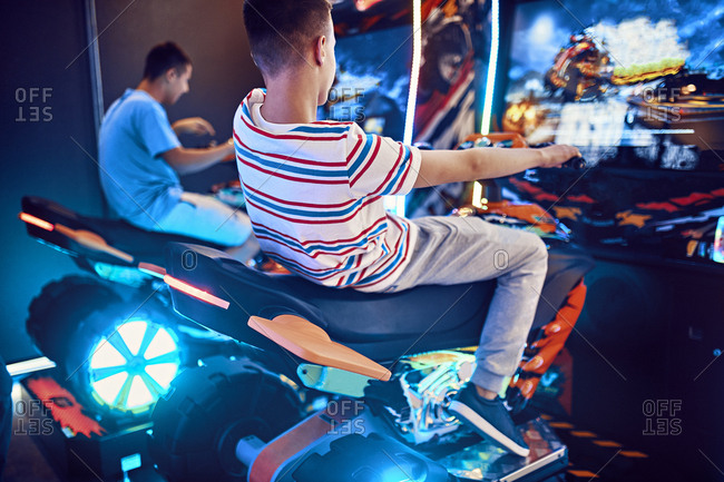 Teenage friends playing with a driving simulator in an amusement arcade