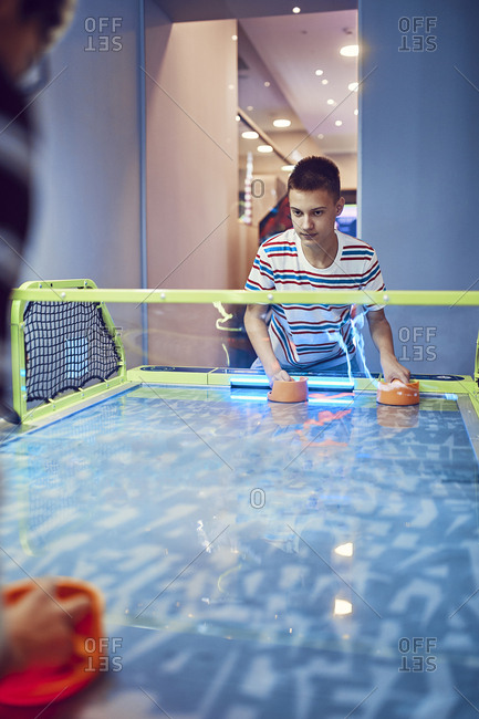 Teenage boy playing air hockey in an amusement arcade