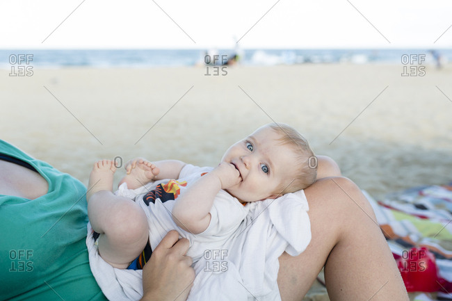 Portrait of cute son with fingers in mouth lying on mother's laps at beach