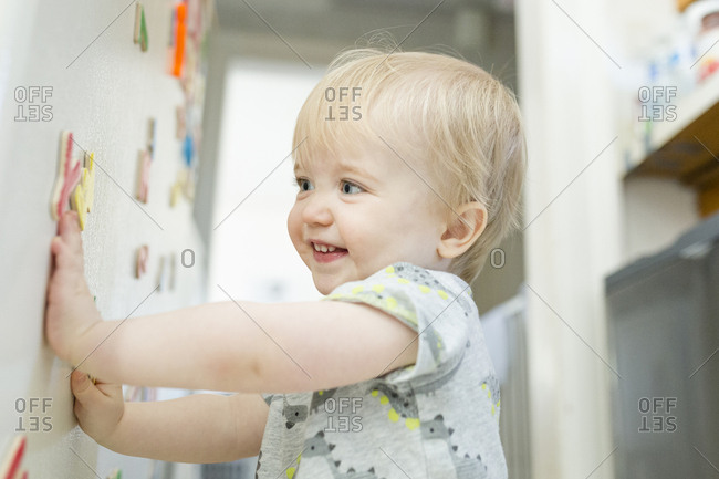 Smiling baby boy playing with colorful magnetic letters on metallic cabinet at home