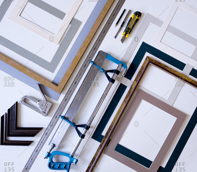Overhead view of picture frames with work tools on table in workshop