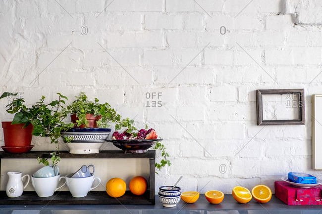 Potted plants and fruits with kitchen utensils on table against brick wall