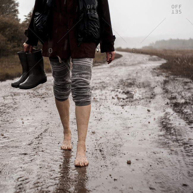 Low section of woman holding rubber boots while walking on wet dirt road