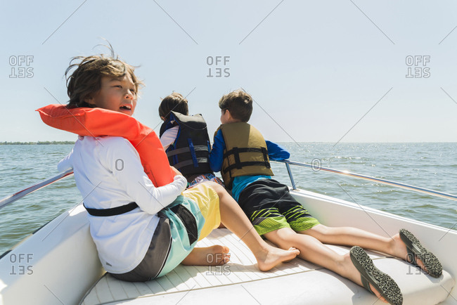 Brothers wearing life jackets traveling in boat against clear sky during sunny day