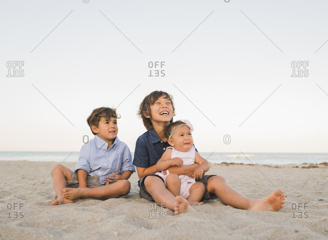 Brothers with sister sitting at beach against clear sky during sunset