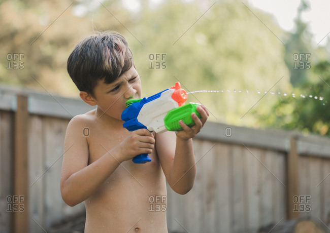 Boy aiming on something with squirt gun while standing in yard