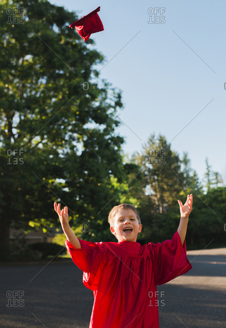 Portrait of happy boy in graduation gown throwing mortarboard on footpath