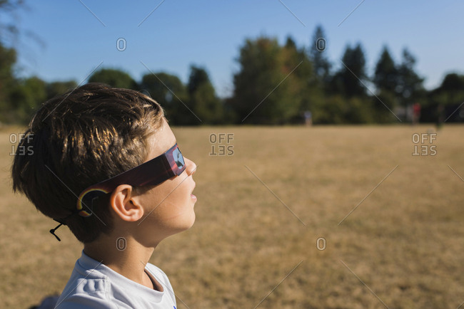 Side view of boy wearing 3-D glasses while looking away at field during sunny day