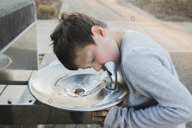Thirsty boy drinking water from fountain at park