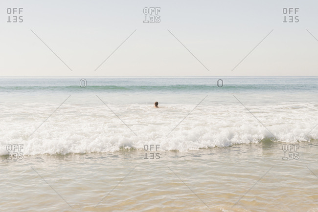 Mid distance view of boy swimming in sea against clear sky