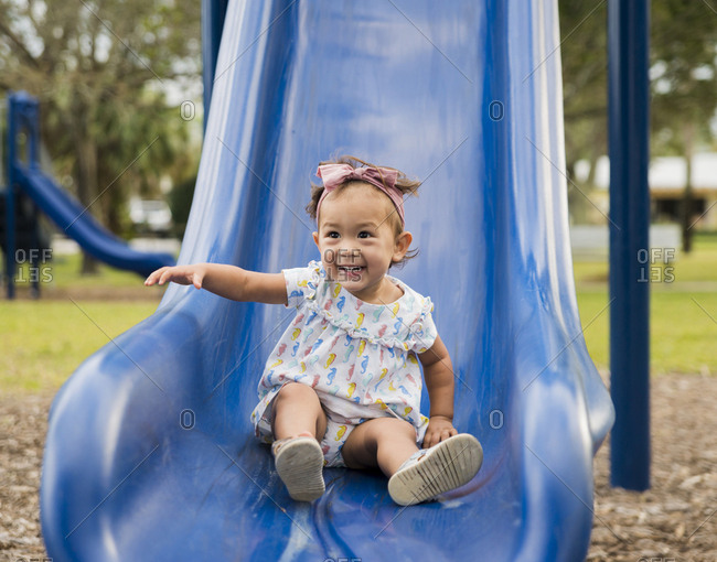 Cute cheerful baby girl sliding on slide at playground