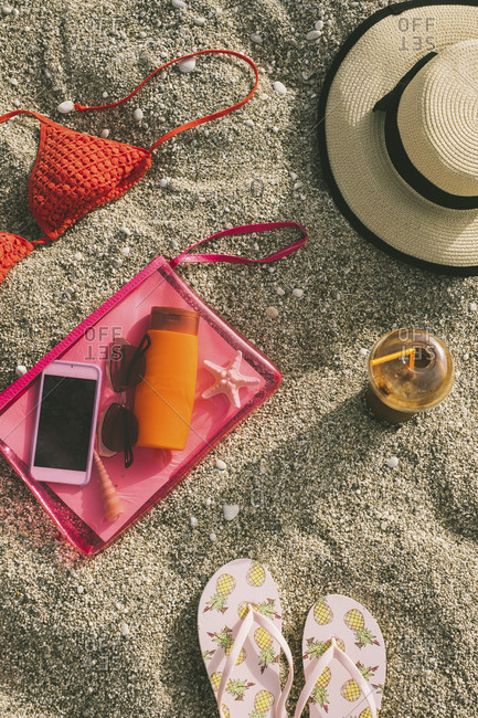 High angle view of beach supplies with smart phone on sand