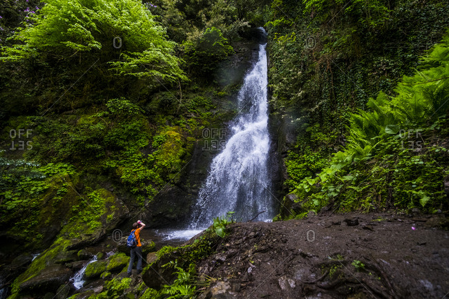 Rear view of hiker photographing waterfall