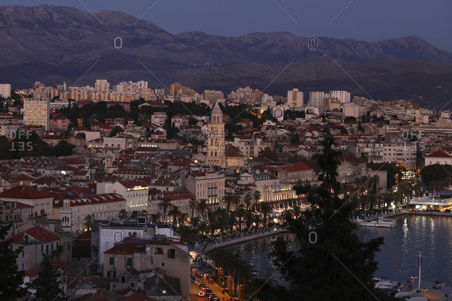 High angle view of buildings in town against mountains at dusk