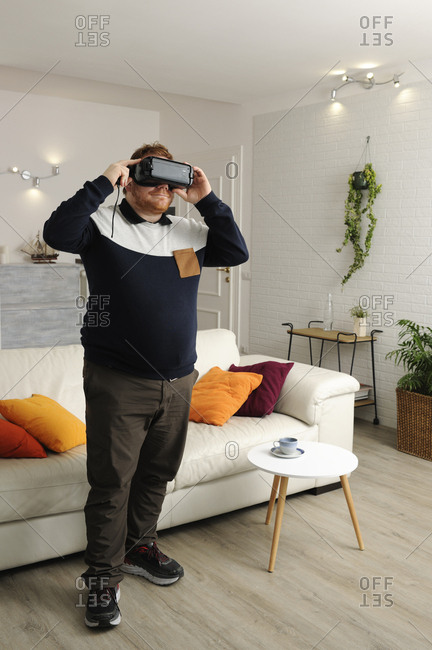 Man looking through virtual reality simulator while standing at home