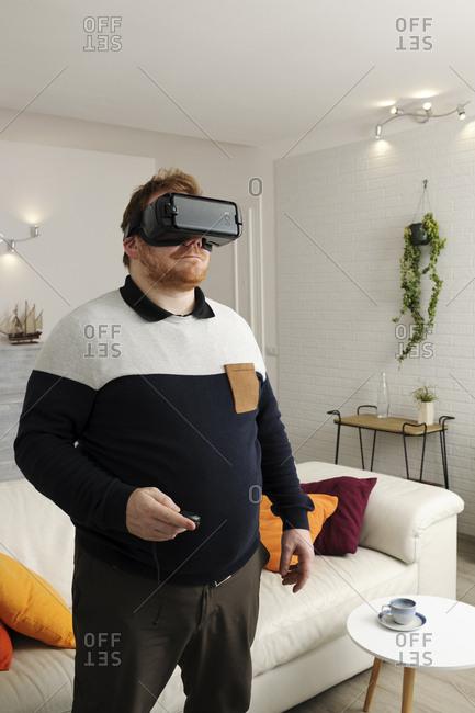Man looking through virtual reality simulator at home