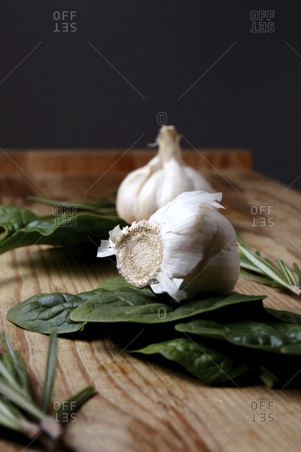 Garlic bulbs with spinach on wooden table against black background