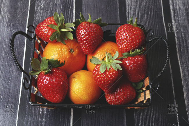 High angle view of strawberries with oranges in container on table