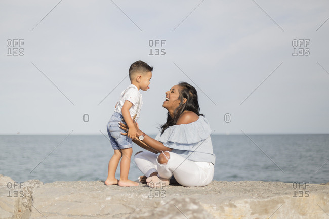 Side view of happy son and mother playing while sitting on retaining wall against sea