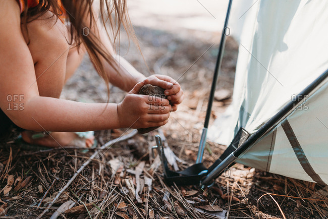 Cropped image of girl hitting stone on tent peg at campsite