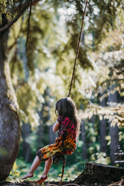 Girl swinging on rope swing at forest