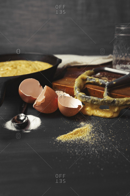 Close-up of messy kitchen counter with broken eggshells and kitchen utensils