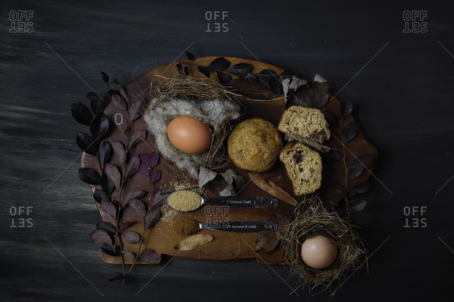 Overhead view of food with twigs on cutting board over wooden table in darkroom