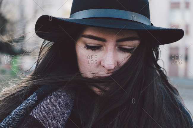 Close-up of thoughtful young woman wearing hat in city