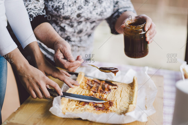 Cropped image of grandmother putting preserves while granddaughter spreading it on bread at home