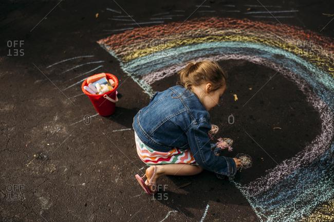 High angle view of carefree girl drawing rainbow on asphalt
