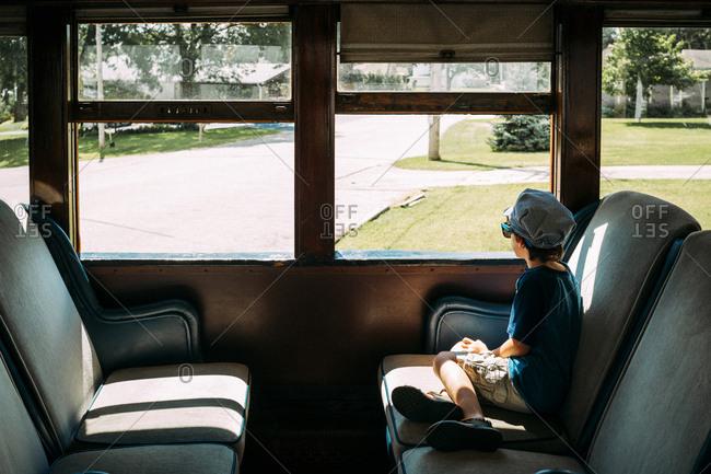 Boy looking through window while sitting in train